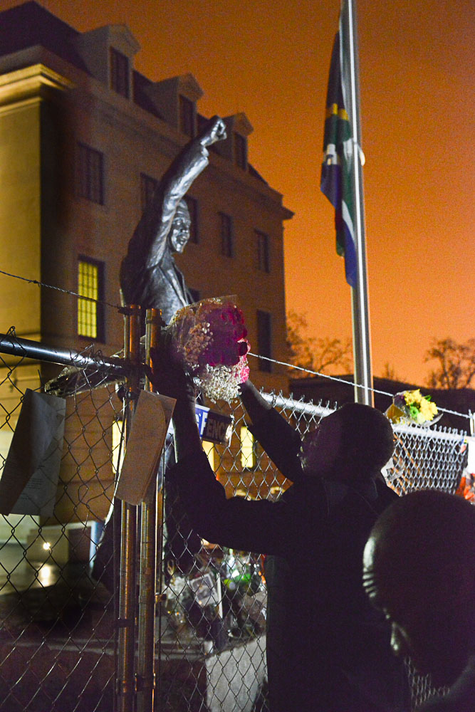 Mourners place flowers in front of a statue of Nelson Mandela outside the South African embassy in Washington DC.  During the latter years of the apartheid an almost continuous stream of anti-apartheid demonstrators was arrested on this spot.