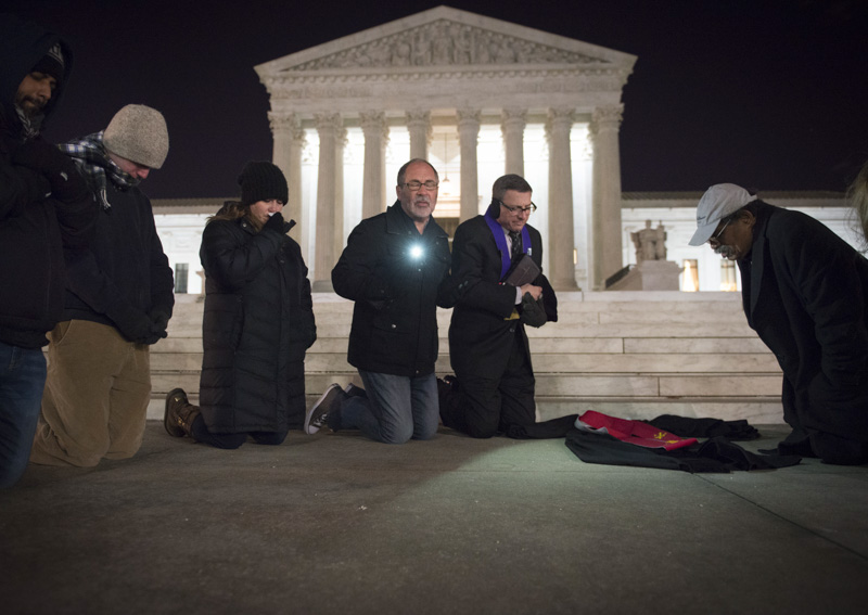 Rev. PATRICK MAHONEY (center, in gray beard and moustache), director of the Christian Defense Coalition and lead pastor of Church on the Hill, leads a candle light vigil in front of the Supreme Court for Justice Antonin Scalia, who died earlier in the day.  The court's flags were at half-staff, while the small prayer group laid out a judge's black robe to represent the late justice.