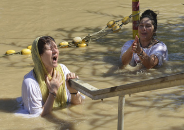 Women are baptized through total immersion in the Jordan River, on the West Bank. Life in Jerusalem, Israel and Palestine is said to be slowly returning to normal following months of attacks in which 28 Israelis and two Americans were killed by Palestinian attacks, one by a bus bombing, and at least 188 Palestinians killed by Israeli fire.